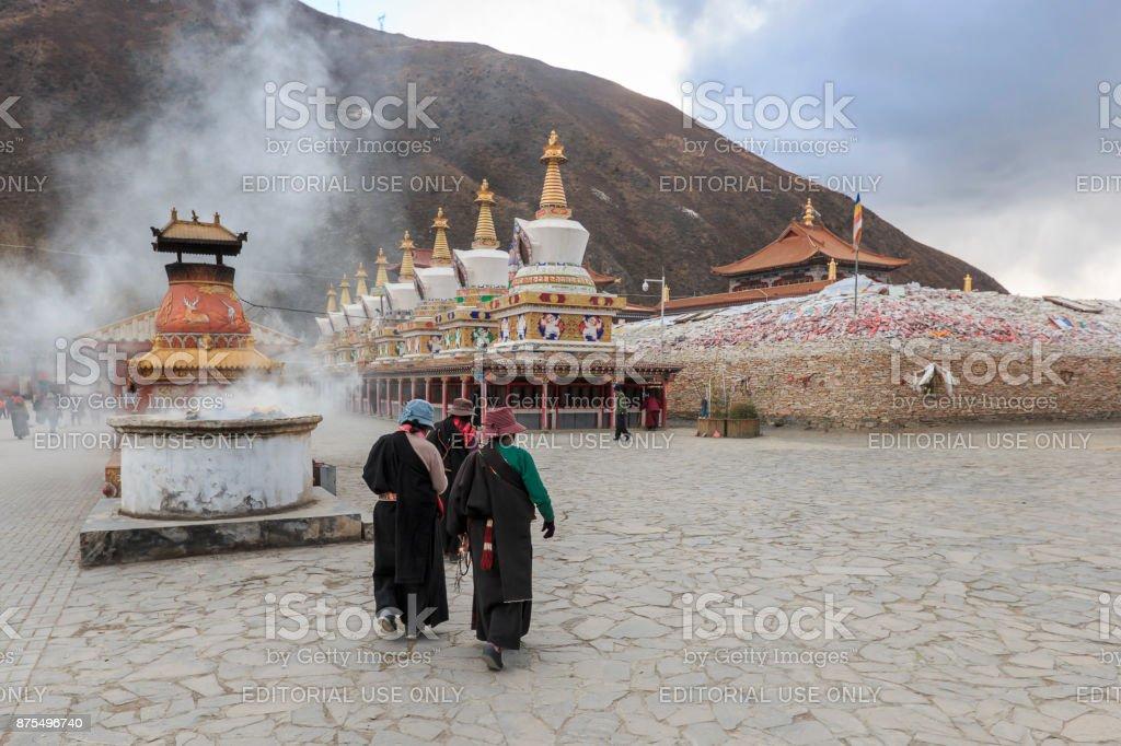 Tibetan people walking around Mani Temple (Mani Shicheng) a famous landmark in the Tibetan city of Yushu (Jyekundo), Qinghai, China. stock photo