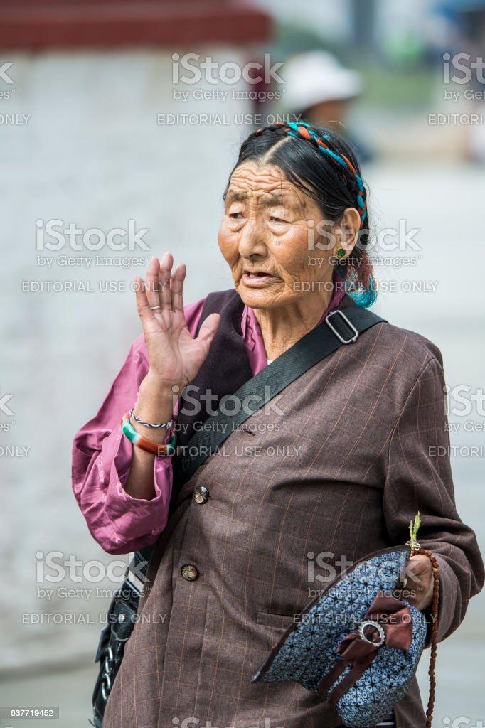 Tibetan pilgrim praying, Barkhor, Lhasa stock photo