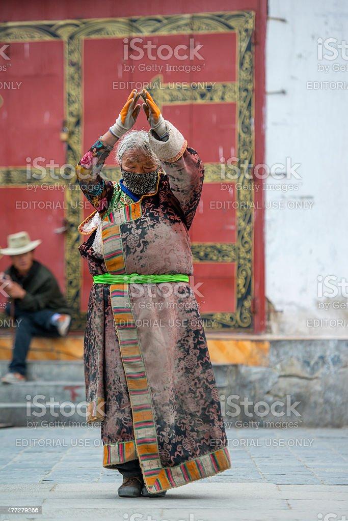 Tibetan pilgrim prostrating at the Barkhor in Lhasa, Tibet. stock photo