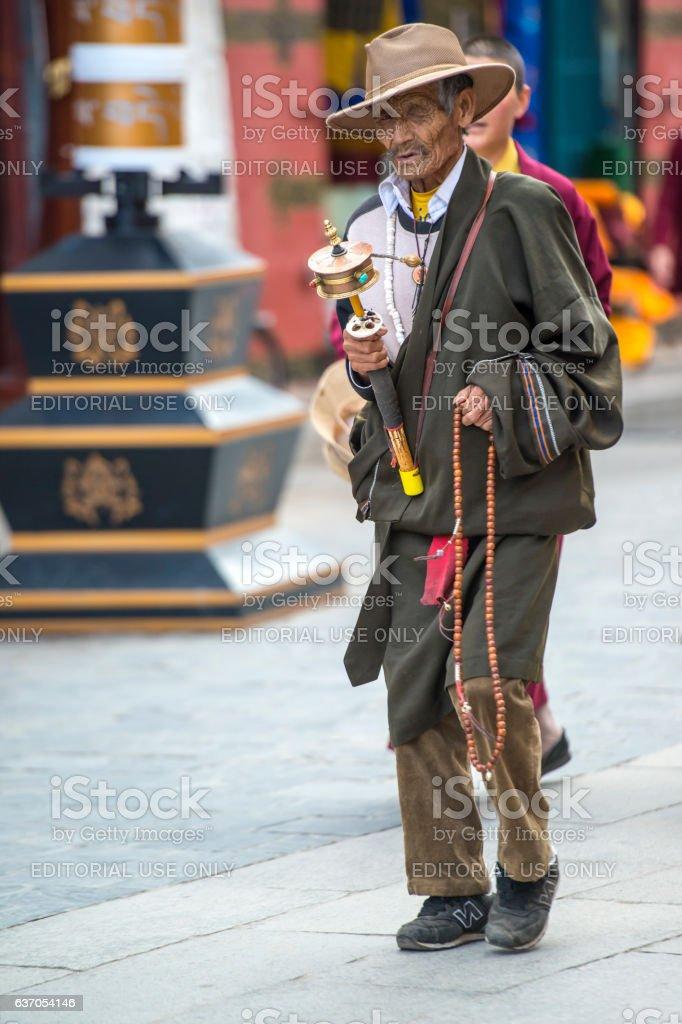 Tibetan pilgrim with prayer wheel at Barkhor, Lhasa, Tibet stock photo