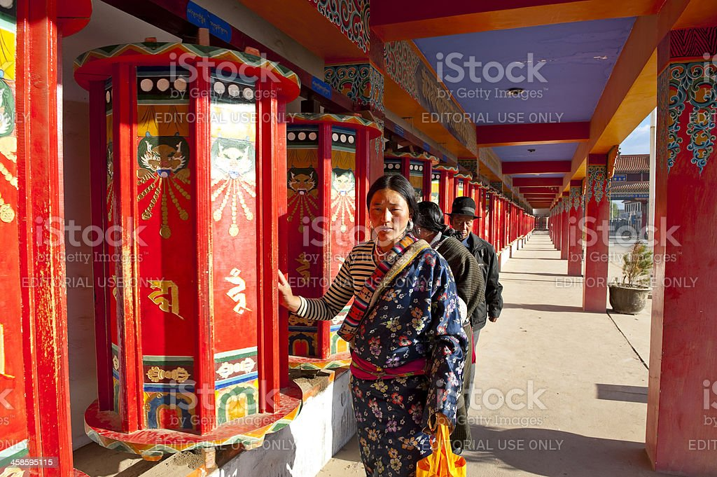 Tibetan pilgrims praying in temple by turning the prayer wheels stock photo