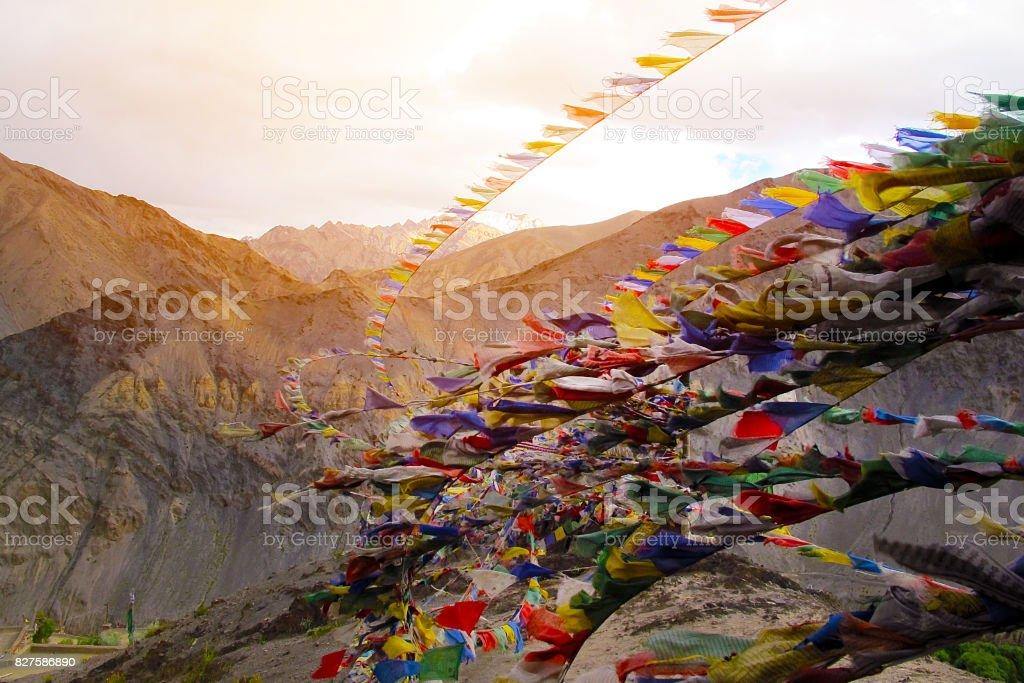 Tibetan prayer mantra flags Lungta fluttering on strong wind on the top of Lamayuru Monastery, Lamayuru India stock photo