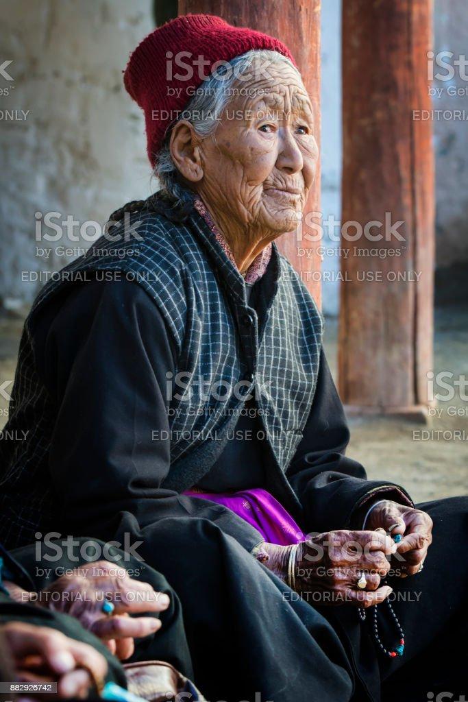 Tibetan senior woman with her buddhist prayer beads stock photo