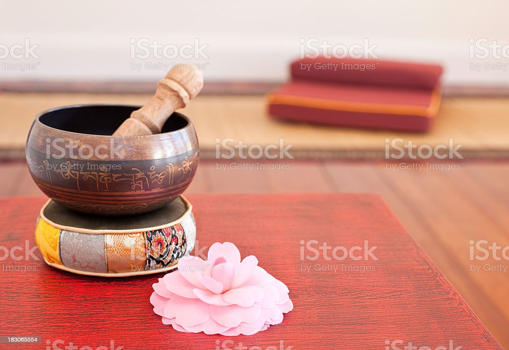 Tibetan singing bowl placed next to a small pale pink flower stock photo