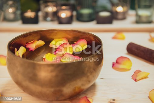 istock Tibetan singing bowl with floating in water flower petals. Special sticks, burning candles, petals on the wooden background. Meditation and Relax treatment. Exotic massage. Selective focus 1299349895