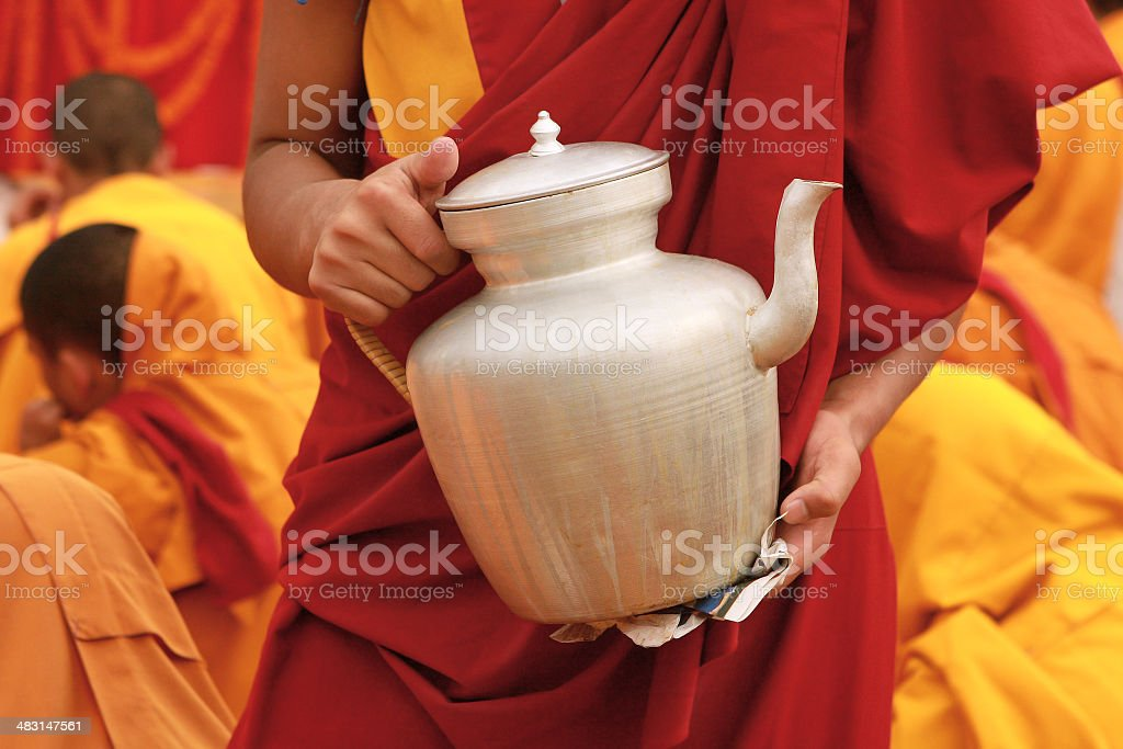 Tibetan tea teapot in the hands of a monk in Nepal royalty-free stock photo