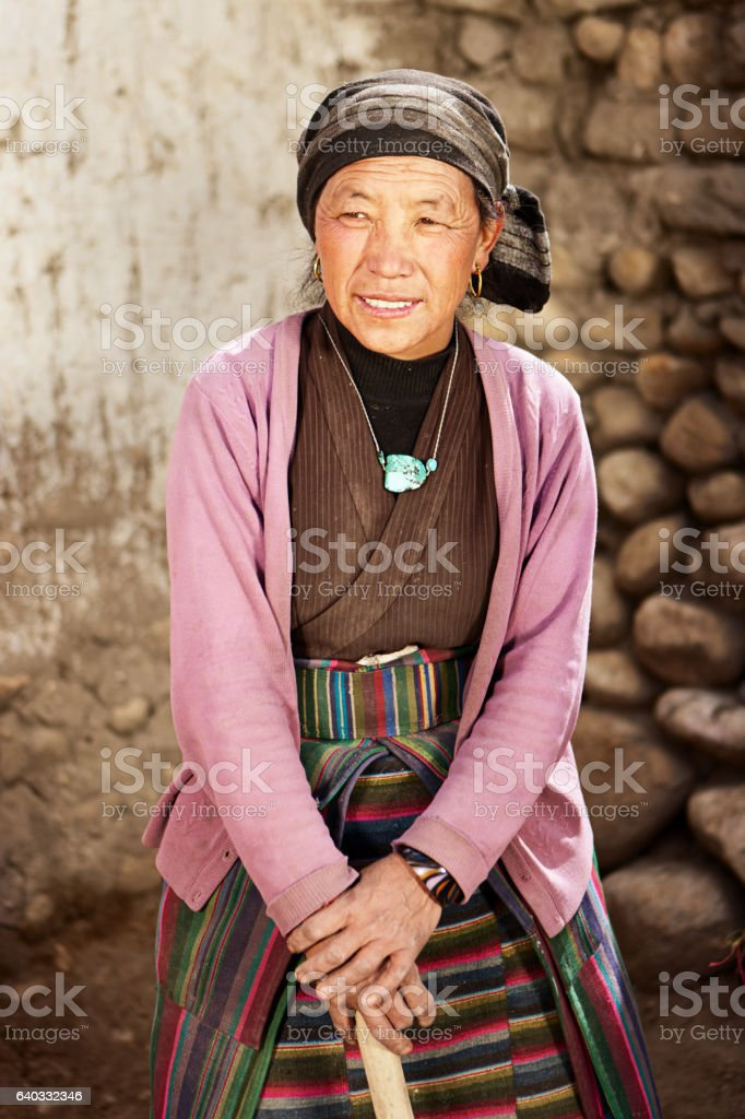Tibetan woman at work. Mustang, Nepal. stock photo