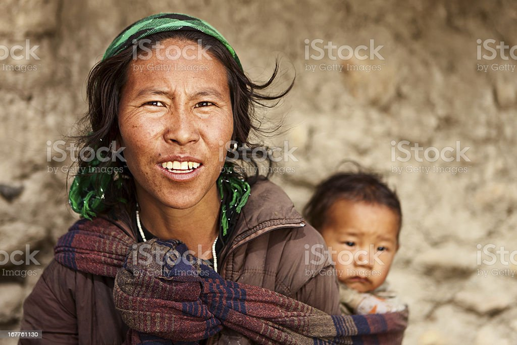 Tibetan woman carrying her baby, Mustang, Nepal stock photo