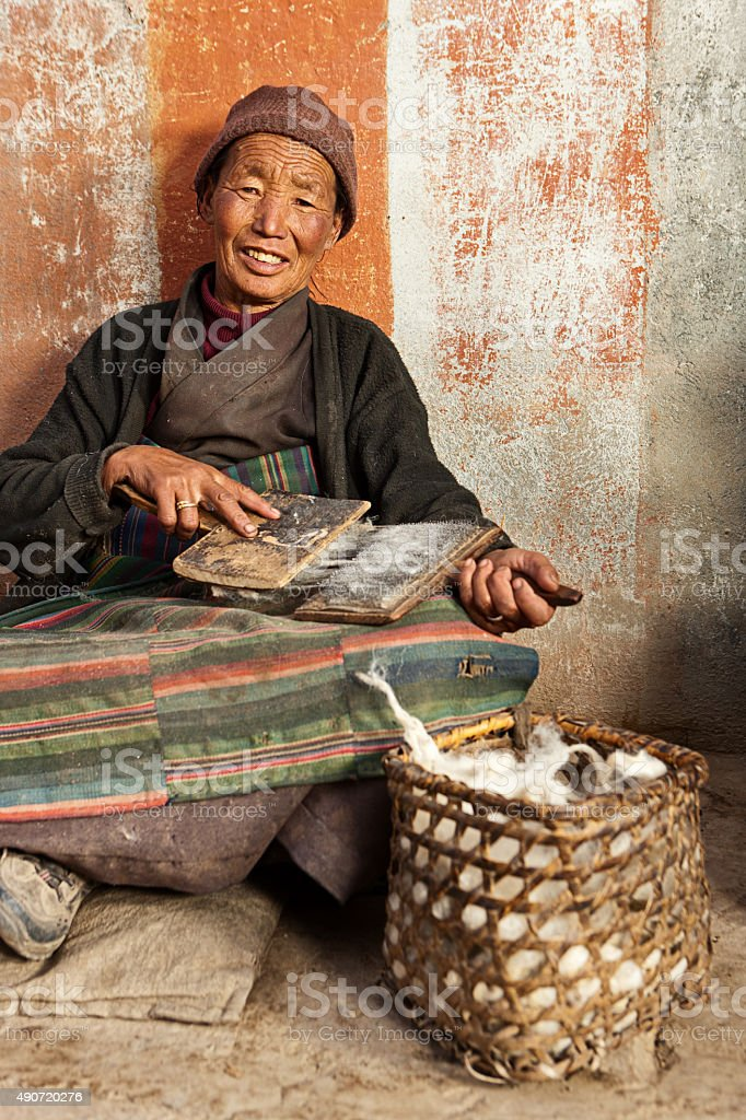 Tibetan woman combing wool in Lo Mantang stock photo