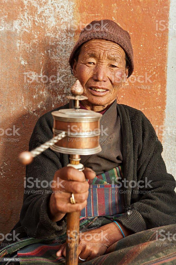Tibetan woman holding praying wheel, Upper Mustang stock photo
