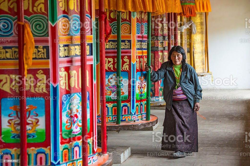 Tibetan woman is turning huge and colorful prayer wheels stock photo