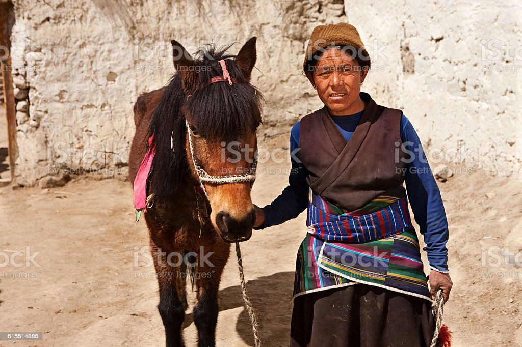 Tibetan woman leads her horse in Upper Mustang stock photo