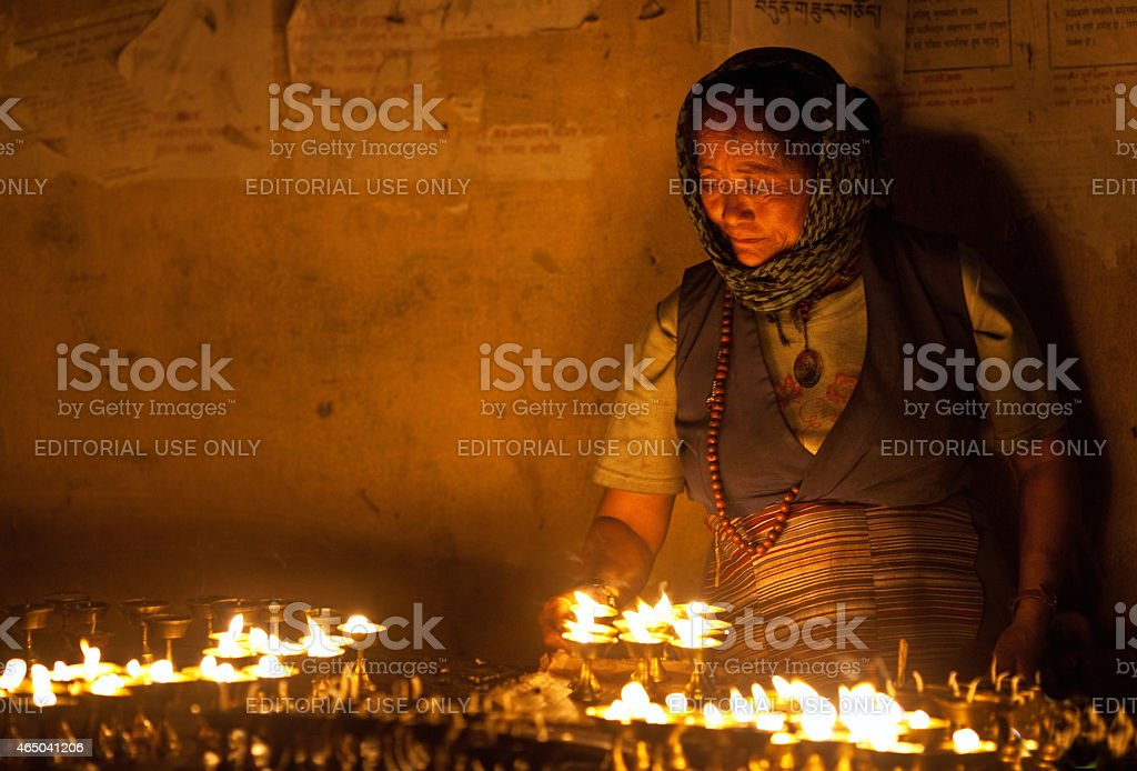 Tibetan woman lights incense butter candles stock photo