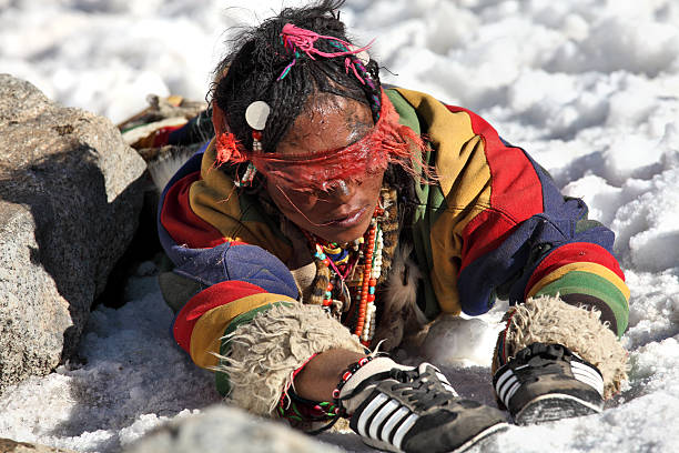 Tibetan woman pilgrim circumambulating Mt. Kailash by full body prostrations Mt Kailash, Tibet, China - May 28, 2012: Tibetan Buddhist woman pilgrim circumambulating Mt. Kailash by performing full body prostrations circumambulation stock pictures, royalty-free photos & images