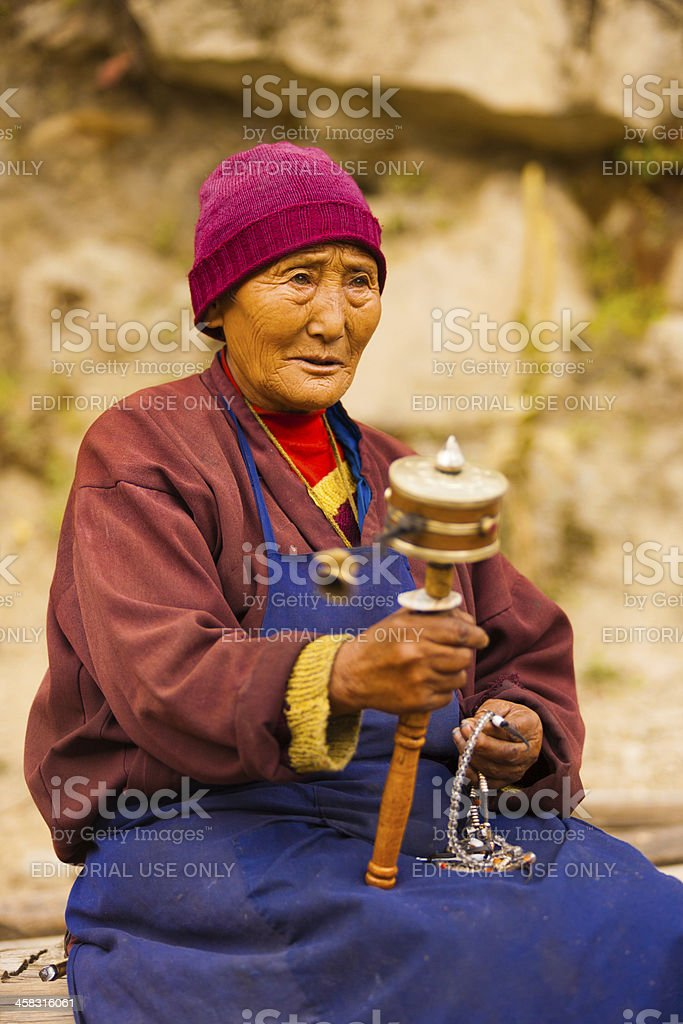 Tibetan Woman Pilgrim Praying Spinning Mani Wheel stock photo