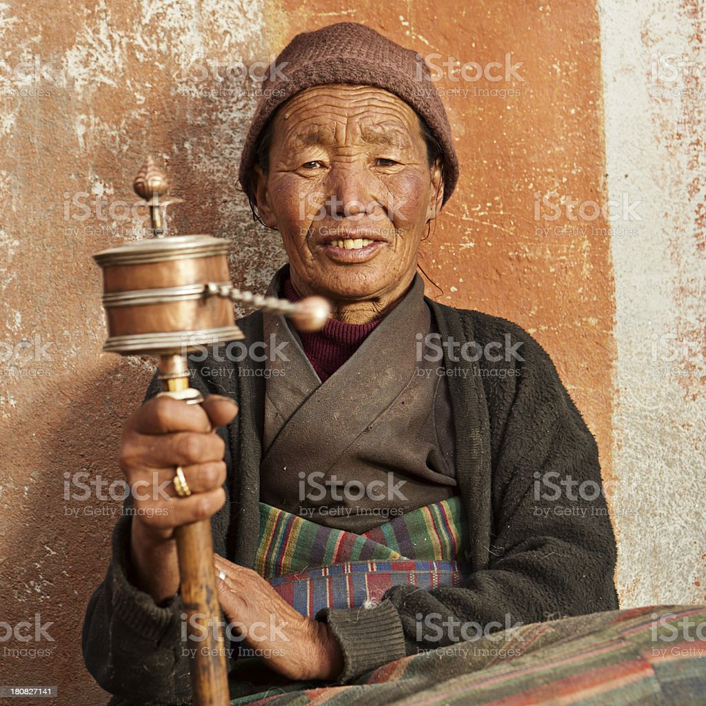 Tibetan woman praying, Mustang stock photo