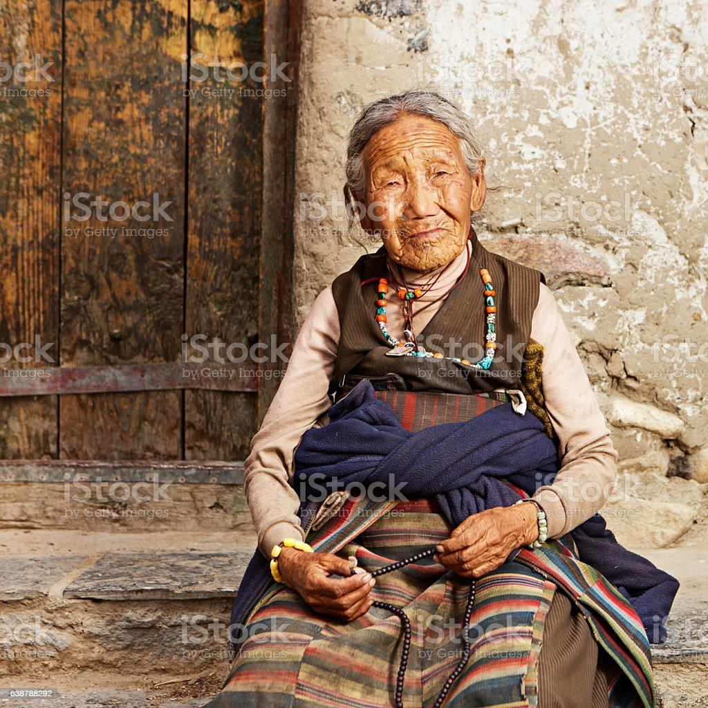 Tibetan woman praying with rosary, near Lo Manthang stock photo