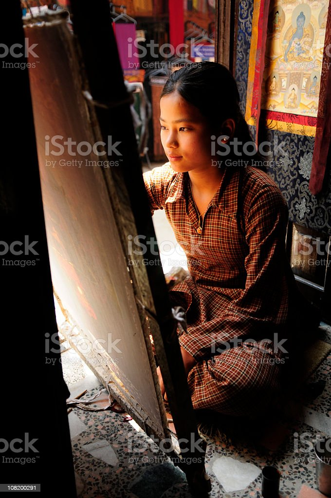 Tibetan Woman Sitting and Painting stock photo