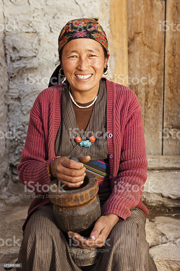 Tibetan woman using a mortar to make  flour. Mustang, Nepal stock photo