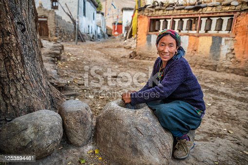 Tibetan woman using a stone mortar to make flour, small village in Upper Mustang. Mustang region is the former Kingdom of Lo and now part of Nepal,  in the north-central part of that country, bordering the People's Republic of China on the Tibetan plateau between the Nepalese provinces of Dolpo and Manang.