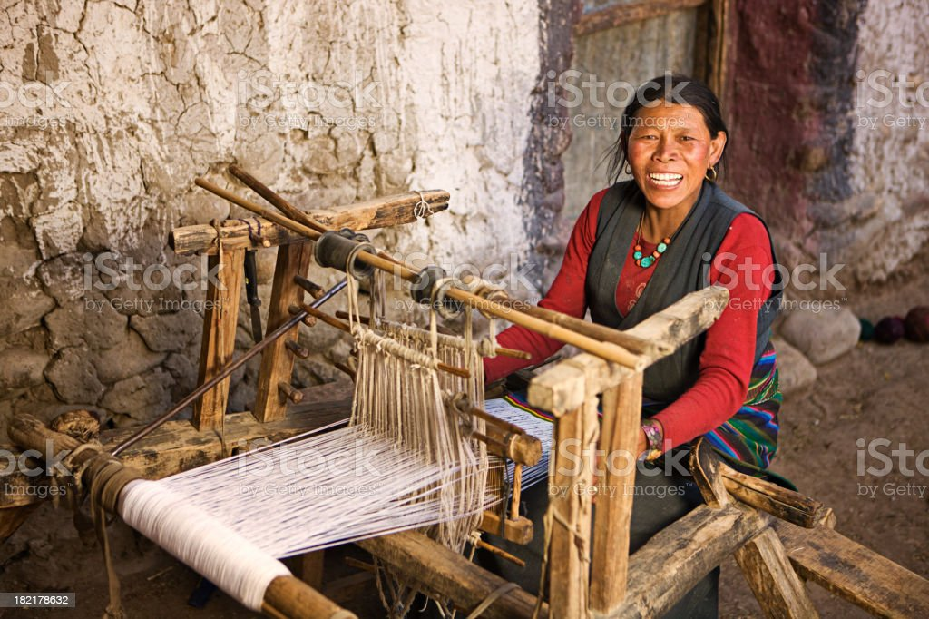 Tibetan woman weaving a carpet stock photo