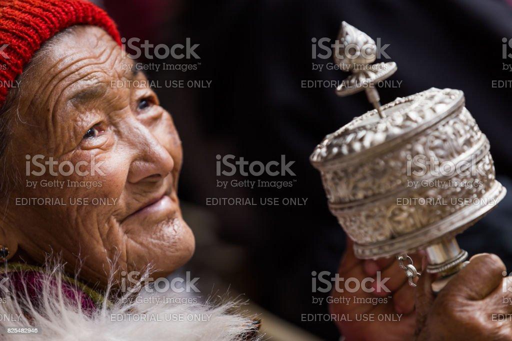 Tibetan woman with Buddhist prayer wheel stock photo
