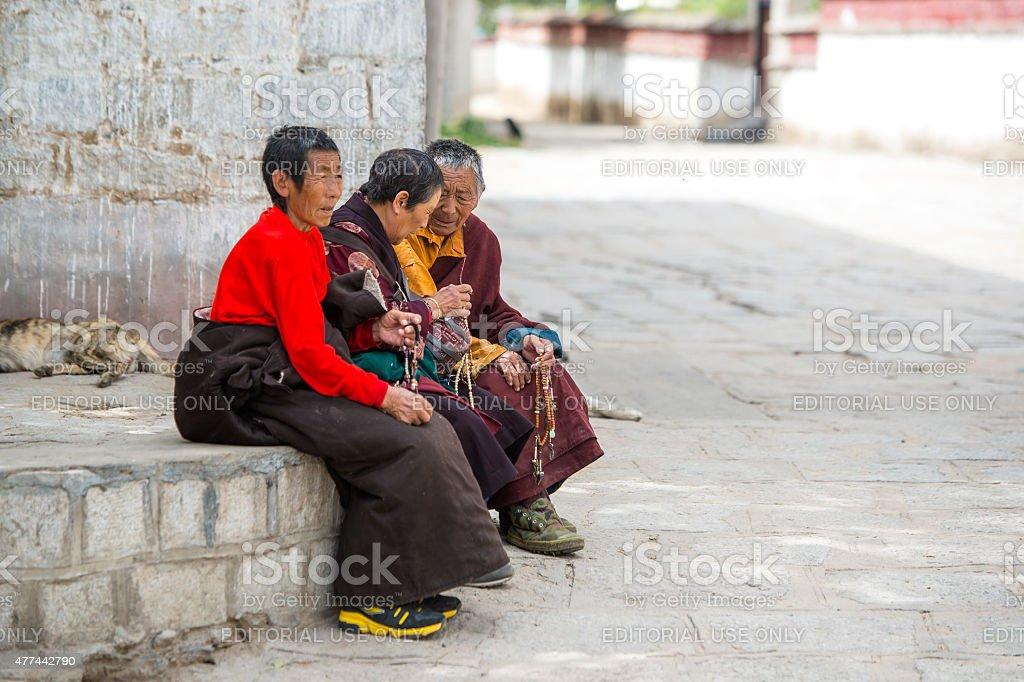 Tibetan women praying with buddhist prayer beads stock photo