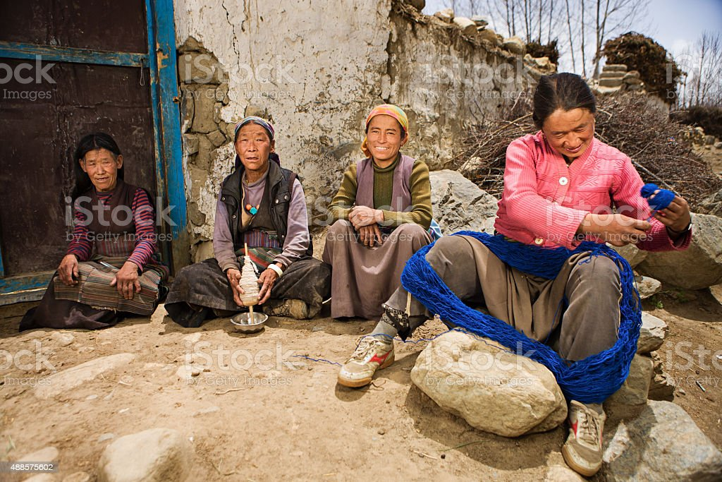 Tibetan women spinning wool in Mustang region stock photo