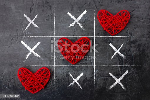 Tic Tac Toe game on Valentine's day against a dark background. View from above