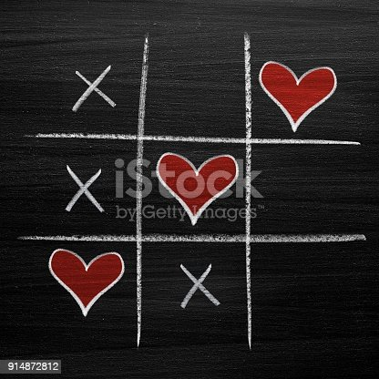 Tic tac toe game with chalk hearts, XO noughts and crosses Valentine's Day style
