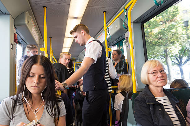 ticket collector on board stockholm tram. - transport conductor stock photos and pictures