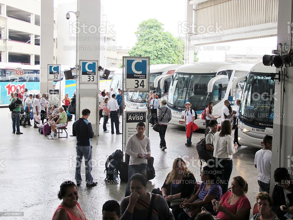 Ticket collector outside Brazilian coach with passengers queing stock photo