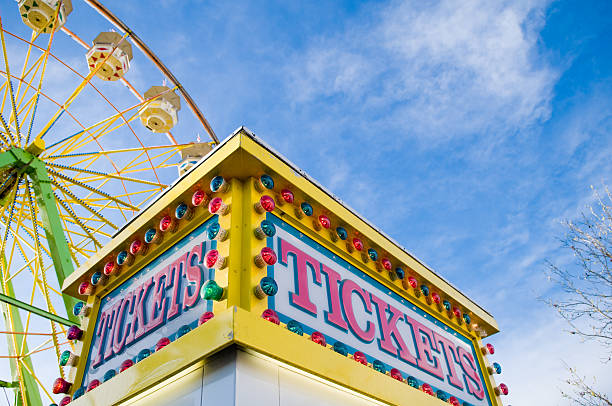 Ticket counter at county faire Tickets sign at county fair with Ferris wheel and light colored blue sky with white clouds in the background. ferris wheel stock pictures, royalty-free photos & images