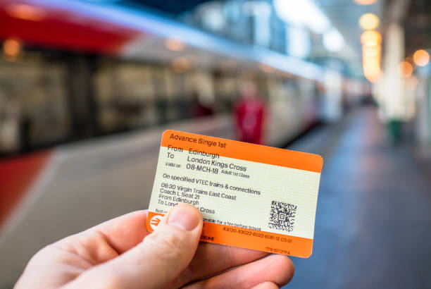 Ticket for British train journey Edinburgh, UK - Close-up of a train ticket from Edinburgh to London King's Cross, with the train waiting on the platform at Edinburgh's Waverley station in the background. train ticket stock pictures, royalty-free photos & images