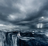 Sailing boat going over the edge in Hurricane conditions. Conceptual.
