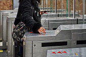 Barcelona, Spain - December 19, 2019: A person validates his subway ticket at a machine and walks through the glass barrier.