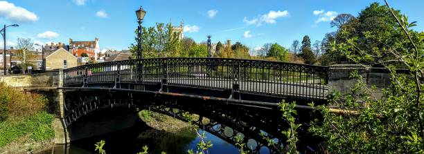 Tickford Bridge Newport Pagnell Panoramic A panoramic view of Tickford Bridge in Newport Pagnell, UK which is the oldest working iron bridge in the world. Church and town scene visible in background,  River Ouse or Lovat in foreground footbridge stock pictures, royalty-free photos & images