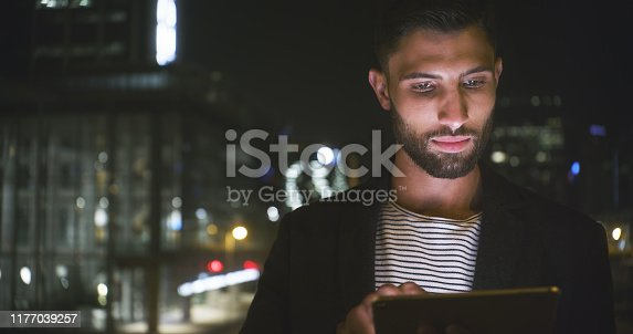 Cropped shot of a handsome young businessman standing alone and using a tablet in the office late at night