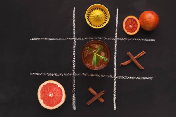 tic tac toe mit orangen und gewürzen auf schwarzem hintergrund - zimt vorteile stock-fotos und bilder