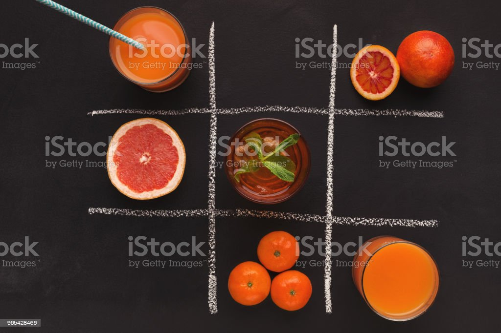 Tic-tac-toe with oranges and spices on black background royalty-free stock photo