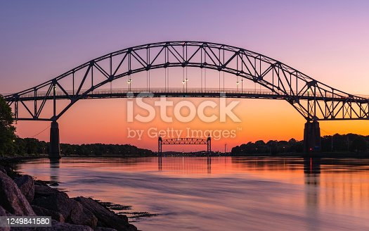 The Bourne Bridge in Bourne, Massachusetts connects Cape Cod with the mainland over the Cape Cod Canal. The tidal change at the canal occurs every six hours or so. This photo was taken approximately one hour after the high tide at 8:43 pm on June 14, 2020.  The architectural structure seen under the bridge at the center is the Cape Cod Canal Railroad Bridge.