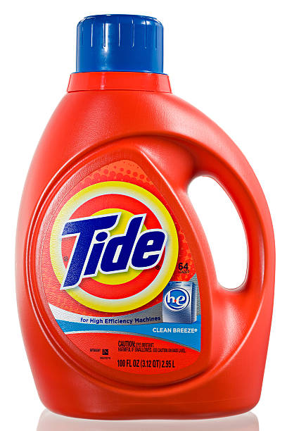 Tide HE Laundry Detergent. Chico, California, USA - March 05,2011 : An orange plastic jug with the Tide logo & containing 100 OZ of Tide HE Laundry Detergent. The HE designation stands for High Efficiency, the detergent was formulated for the the new energy efficient front loading washing machines which require an average of 1.5 OZ of detergent per load. Tide is one of the many fine brands of the Procter & Gamble corporation. laundry detergent stock pictures, royalty-free photos & images