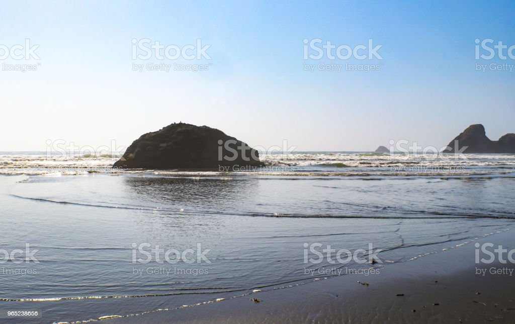 Tide lapping at the shore with huge rocks jutting out of the ocean royalty-free stock photo