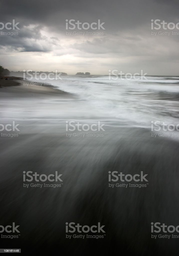 Tide on Black Sand Beach Shore with Storm Clouds Above stock photo