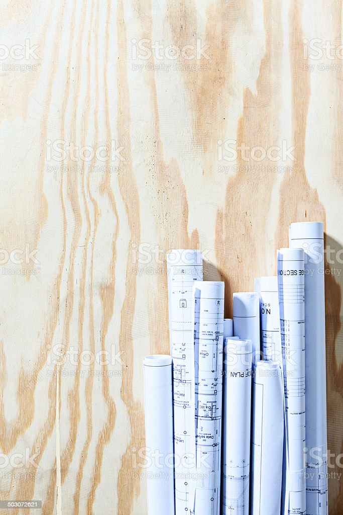 Tidily rolled blueprints form bottom border on wooden background royalty-free stock photo