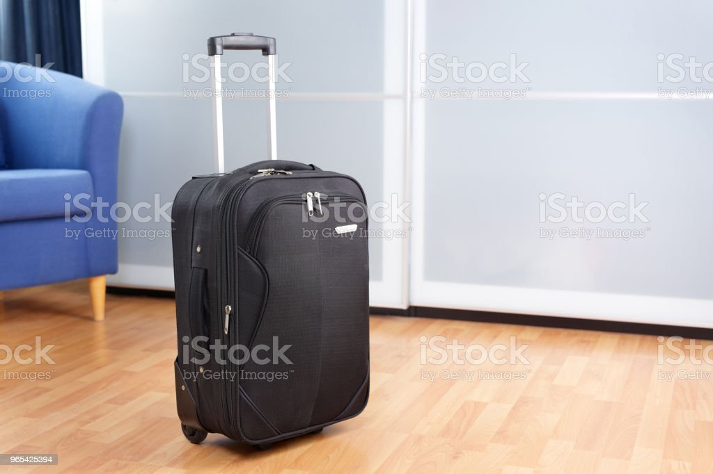 Tidy room with packed roller suitcase in front of closet royalty-free stock photo