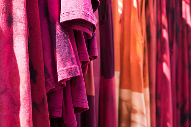 tie dyed t-shirts and dresses hanging out for display stock photo