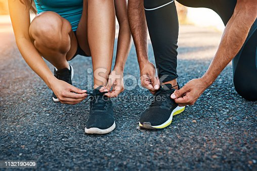 Cropped shot of an unrecognizable young couple tying their shoelaces while out for a run