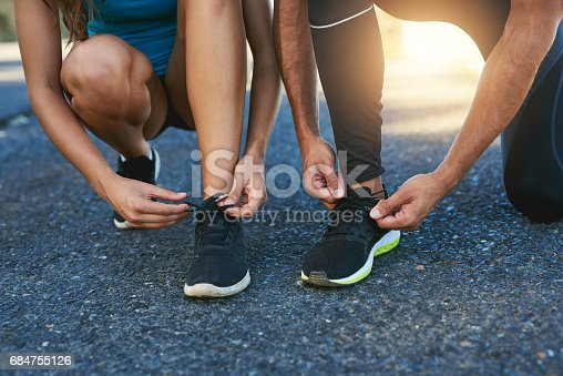 Cropped shot of a couple tying their shoelaces while out for a run