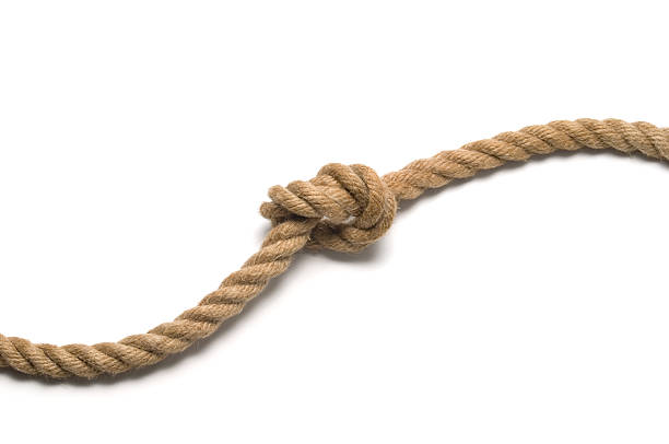 Tied knot on old rope stock photo